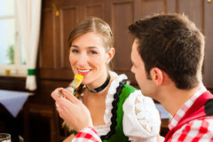 Couple in Bavarian Tracht eating in restaurant Stock Photos