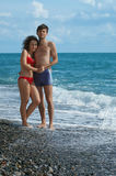 Couple on the beach. Young man and woman standing embraced on the beach Royalty Free Stock Photo
