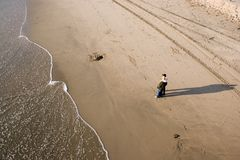Couple on beach. Two people standing on beach staring out over water Royalty Free Stock Image