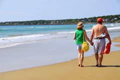 Couple beach. Mature couple walking on a sandy beach holding hands Royalty Free Stock Photo
