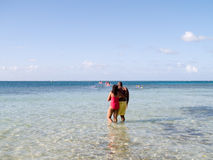Couple At The Beach. Afro-American couple in the clear Caribbean ocean watching wave runners Stock Photography