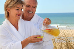Couple on the beach. In matching bath robes Stock Photos