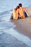Couple at the beach. Outdoor portrait of beautiful romantic couple of topless girl and muscular guy in jeans sitting back to camera on beach Stock Images