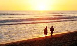 Couple on the beach. An afternoon stroll on the beach on a chilly autumn day Stock Photos