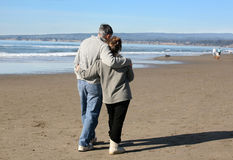 Couple on the beach. A mature couple on walking the beach stock photo