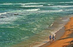Couple on the Beach. A couple walks together on a deserted beach Stock Photography