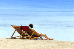 Couple on the beach. Man and woman in chairs resting on the beach near sea Royalty Free Stock Photography