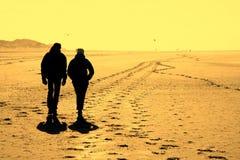 Couple on beach. Couple walking on  a beach in evening sunlight Stock Image