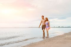 Couple on the beach. Asian couple walking on the beach when the sun is about to sunset during the honeymoon. There are  Couple walking on Valentine`s Day Royalty Free Stock Image