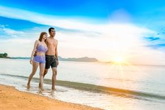 Couple on the Beach. Asian couple walking on the beach when the sun is about to sunset during the honeymoon. There are  Couple walking on Valentine`s Day Stock Images