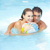 Couple with beach ball in pool Royalty Free Stock Photos