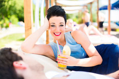 Couple in beach bar relaxing with drinks Stock Photos