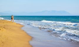 The couple on the beach. The couple on the beautiful sandy Kaiafas beach, Greece royalty free stock images