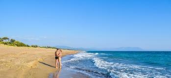 The couple on the beach. The couple on the beautiful sandy Kaiafas beach, Greece royalty free stock photo