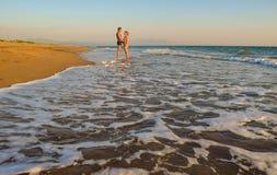 The couple on the beach. The couple on the beautiful sandy Kaiafas beach at sunset, Greece royalty free stock photography