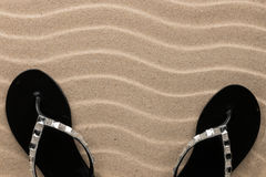 Couple beach black flip flops encrusted with rhinestones standing on the sand. With space for your text royalty free stock photography