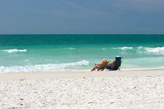 Couple In Beach Chairs. Middle-aged couple lounging at the water's edge on the Treasure Island, Florida public beach Royalty Free Stock Image
