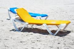 A couple of beach chairs in a deserted beach. A couple of beach chairs in the sand in a deserted beach Stock Photo