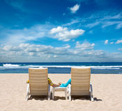 Couple in beach chairs holding hands Stock Image