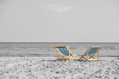 Couple of beach chairs look outward to the sea over black and wh Royalty Free Stock Images