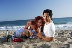 Couple at the beach with champagne and red roses Royalty Free Stock Photos