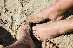 Couple on the beach. Close up legs image royalty free stock photos