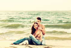 Couple at the beach. Colorized vintage outdoor portrait of beautiful romantic couple of topless girl and muscular guy in jeans on beach Royalty Free Stock Photo