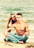 Couple at the beach. Colorized vintage outdoor portrait of beautiful romantic couple of topless girl and muscular guy in jeans on beach Stock Photos