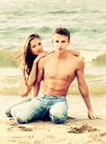 Couple at the beach. Colorized vintage outdoor portrait of beautiful romantic couple of topless girl and muscular guy in jeans on beach Stock Image