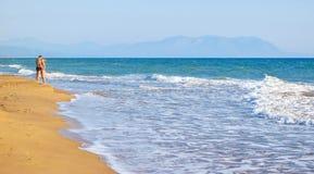 The couple on the beach. The couple on the beautiful sandy Kaiafas beach, Greece royalty free stock image