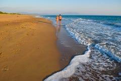 The couple on the beach. The couple on the beautiful sandy Kaiafas beach at sunset, Greece stock photo