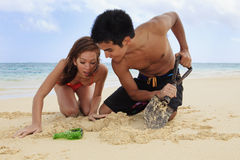Couple on the beach digging. Couple on the beach in hawaii digging for buried treasure stock image