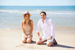 Couple at the beach drawing in the sand. Portrait of a good looking young couple having a good time at the beach and drawing on the sand Stock Photography