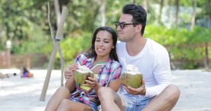 Couple On Beach Drink Coconut Cocktail Talking Sit Under Palm Trees, Happy Man And Woman Tourists Communication. Slow Motion 60 stock video