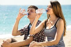 Couple on the beach drinking fresh water Stock Photo