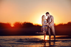 Couple on the beach in the evening Stock Photos