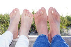 Couple at the Beach with feet in the summer sunlight. Couple at the Beach with feet in the bright summer sunlight Royalty Free Stock Image