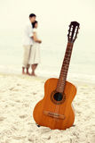Couple at the beach and guitar. Royalty Free Stock Image