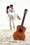 Couple at the beach and guitar. Stock Photo