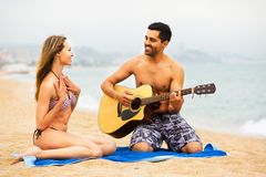 Couple on the beach with guitar Stock Photo