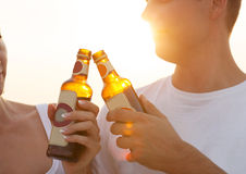 Couple on the beach having party, drinking and having fun. In the sunset holding bottles in their hands with the sun shining through Royalty Free Stock Images