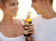 Couple on the beach having party, drinking and having fun in the. Sunset holding bottles in their hands with the sun shining through Royalty Free Stock Photography