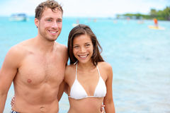 Couple on beach on Hawaii. Happy multicultural multi-ethnic young lovers and friends having fun in swimwear and bikini after swimming in ocean on summer Stock Photo