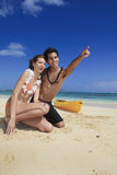 Couple on the beach in hawaii pointing Royalty Free Stock Photos