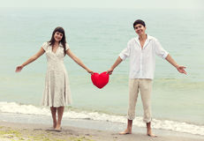 Couple at the beach with heart. Royalty Free Stock Images