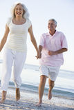 Couple at the beach holding hands and smiling Stock Photo
