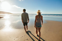 Couple on beach holiday in summertime. Rear view shot of young men and women walking on seashore. Couple on beach holiday in summertime Royalty Free Stock Photo