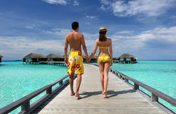 Couple on a beach jetty at Maldives. Couple on a tropical beach jetty at Maldives Royalty Free Stock Photography