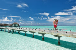Couple on a beach jetty at Maldives. Couple on a tropical beach jetty at Maldives Royalty Free Stock Photos