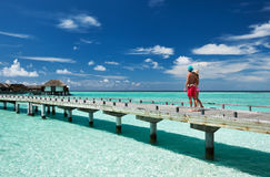 Couple on a beach jetty at Maldives. Couple on a tropical beach jetty at Maldives Royalty Free Stock Images